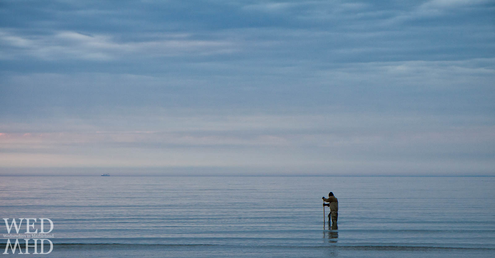 A person digs for clams in the water at dawn in the ocean