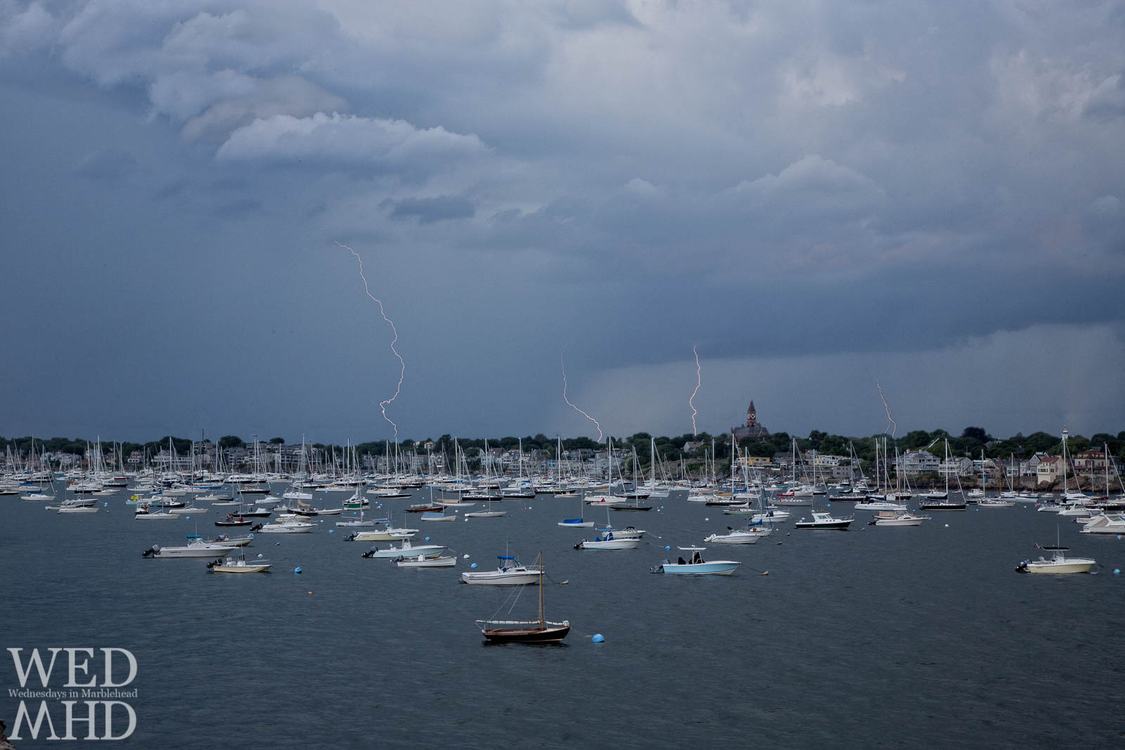 lightning over harbor with boats