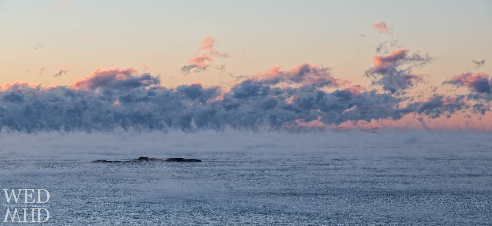 tom moore rock is surrounded by sea smoke