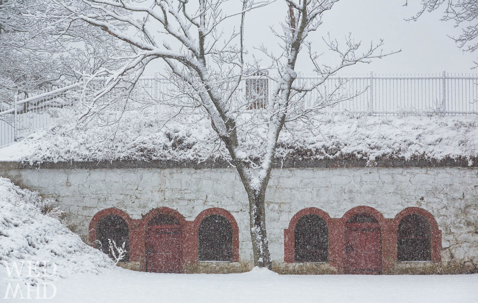 snow falls over red doors at Fort Sewall