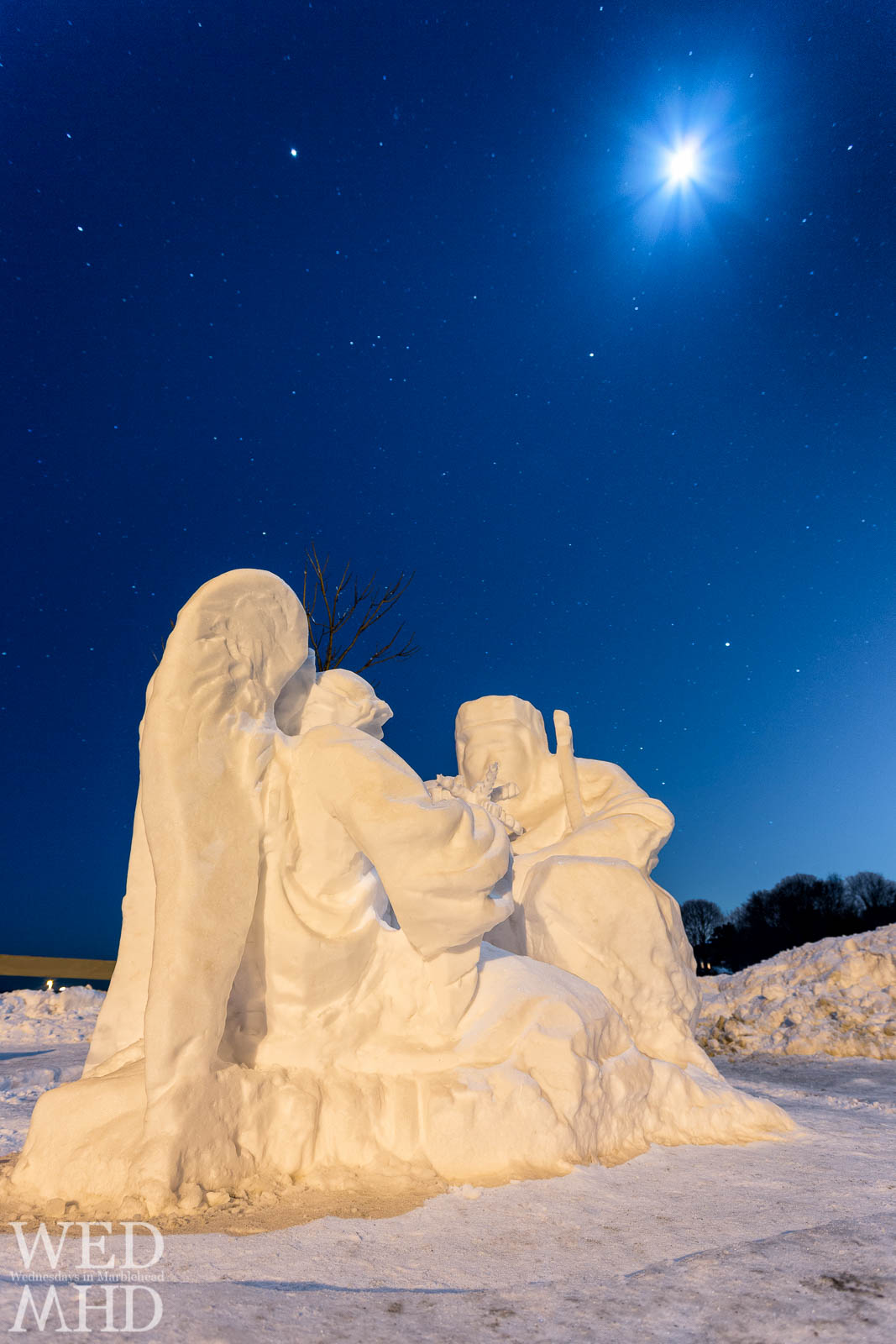 A snow sculpture by artist Jonathan Sherman features an angel presenting a snowflake for a blessing