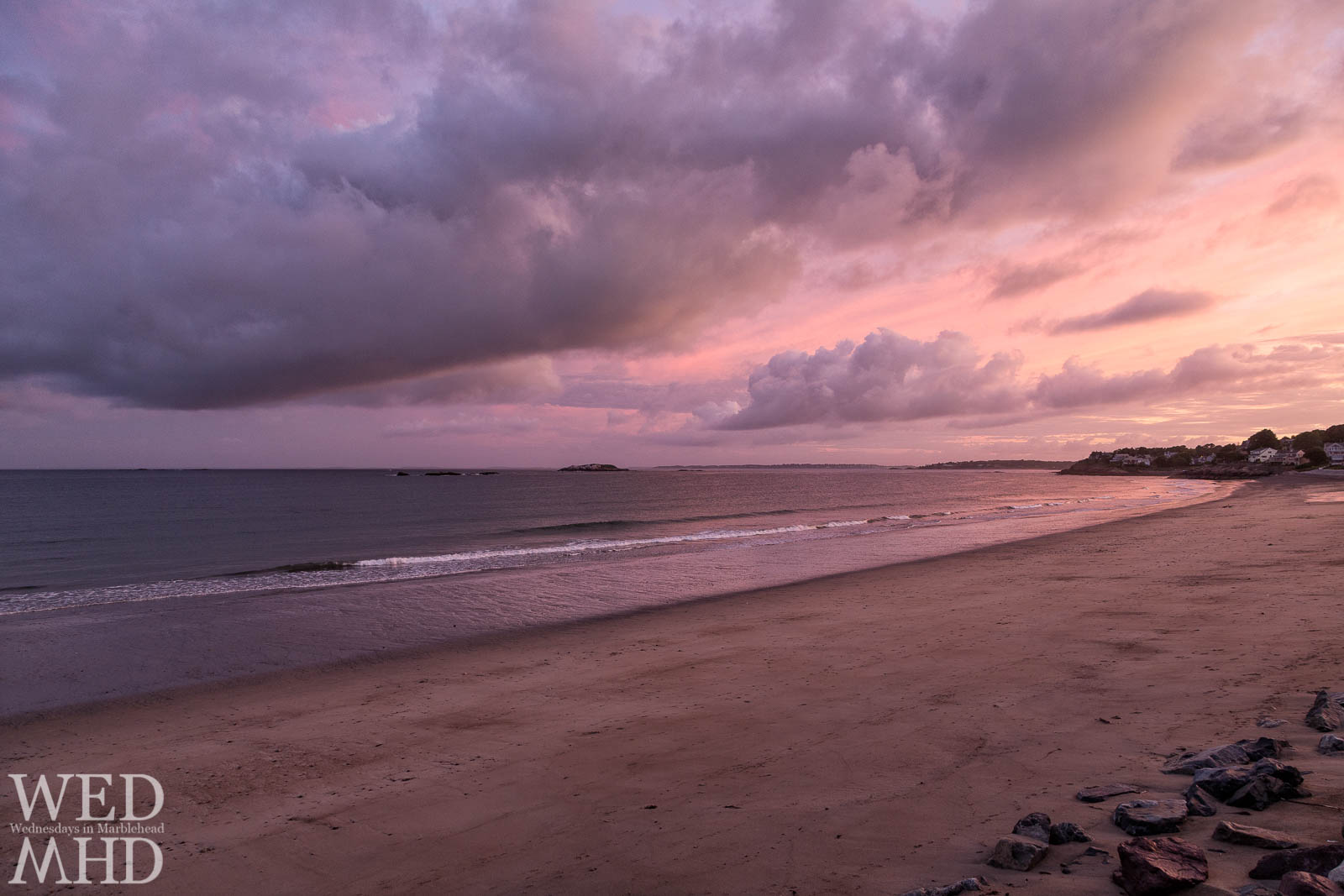 An intense purple sunset takes place over an unusually smooth Devereux Beach
