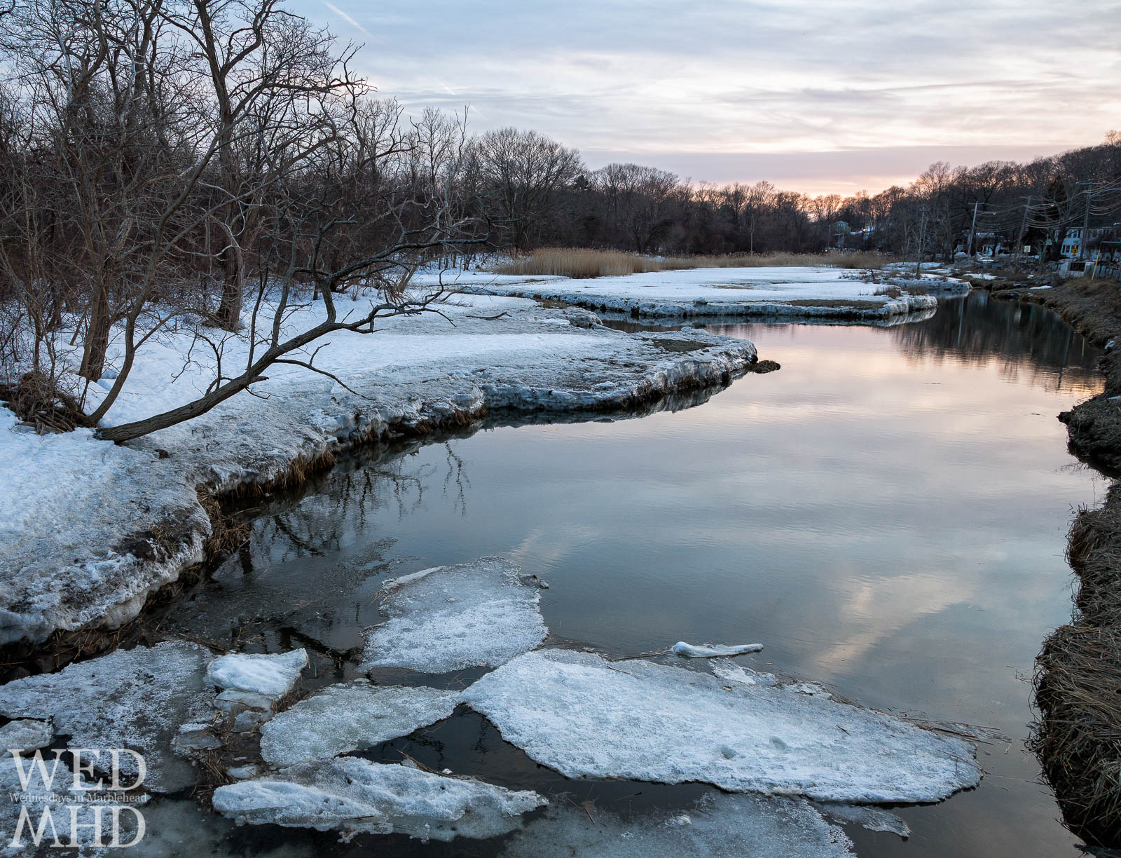 sunset light reflects on the Forest River with cracked ice floating in the water