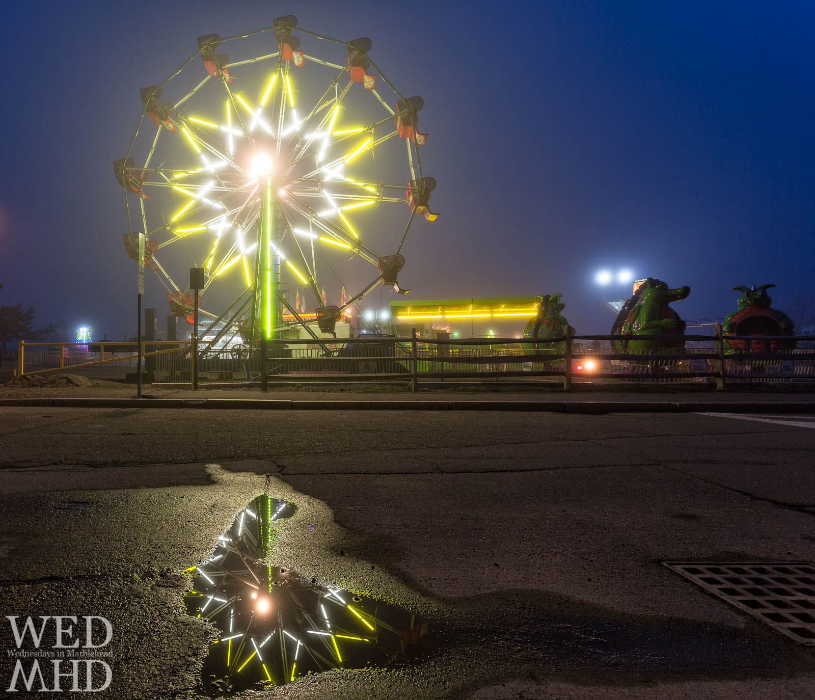 Ferris wheel reflected in a puddle of water on the first night of the carnival