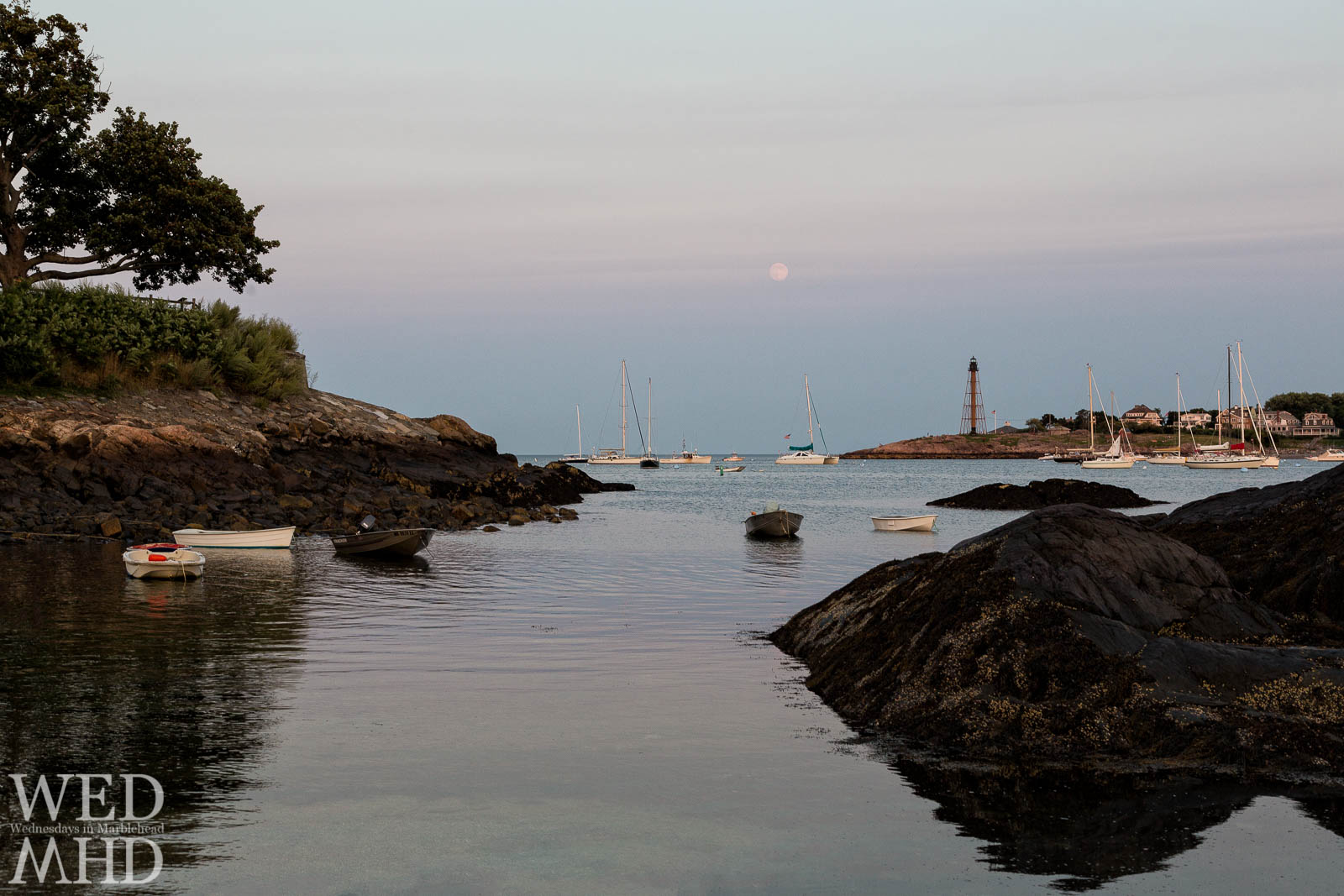 moon rises over lighthouse from Fort Beach in Marblehead