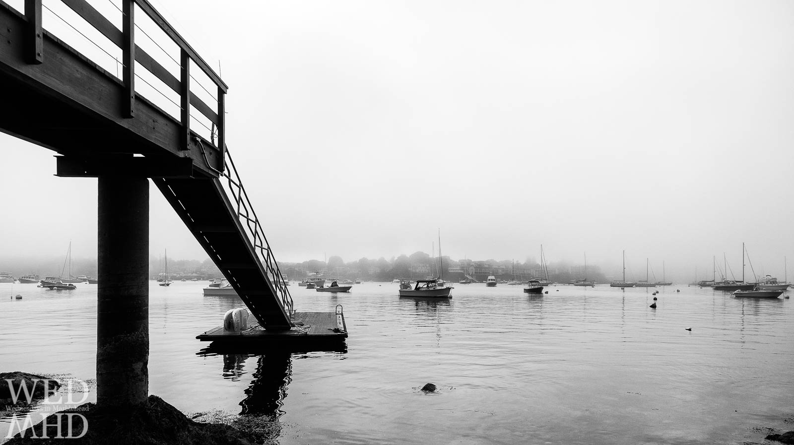 Boats moored in Marblehead Harbor seen on a foggy evening from the beach at Parker Lane