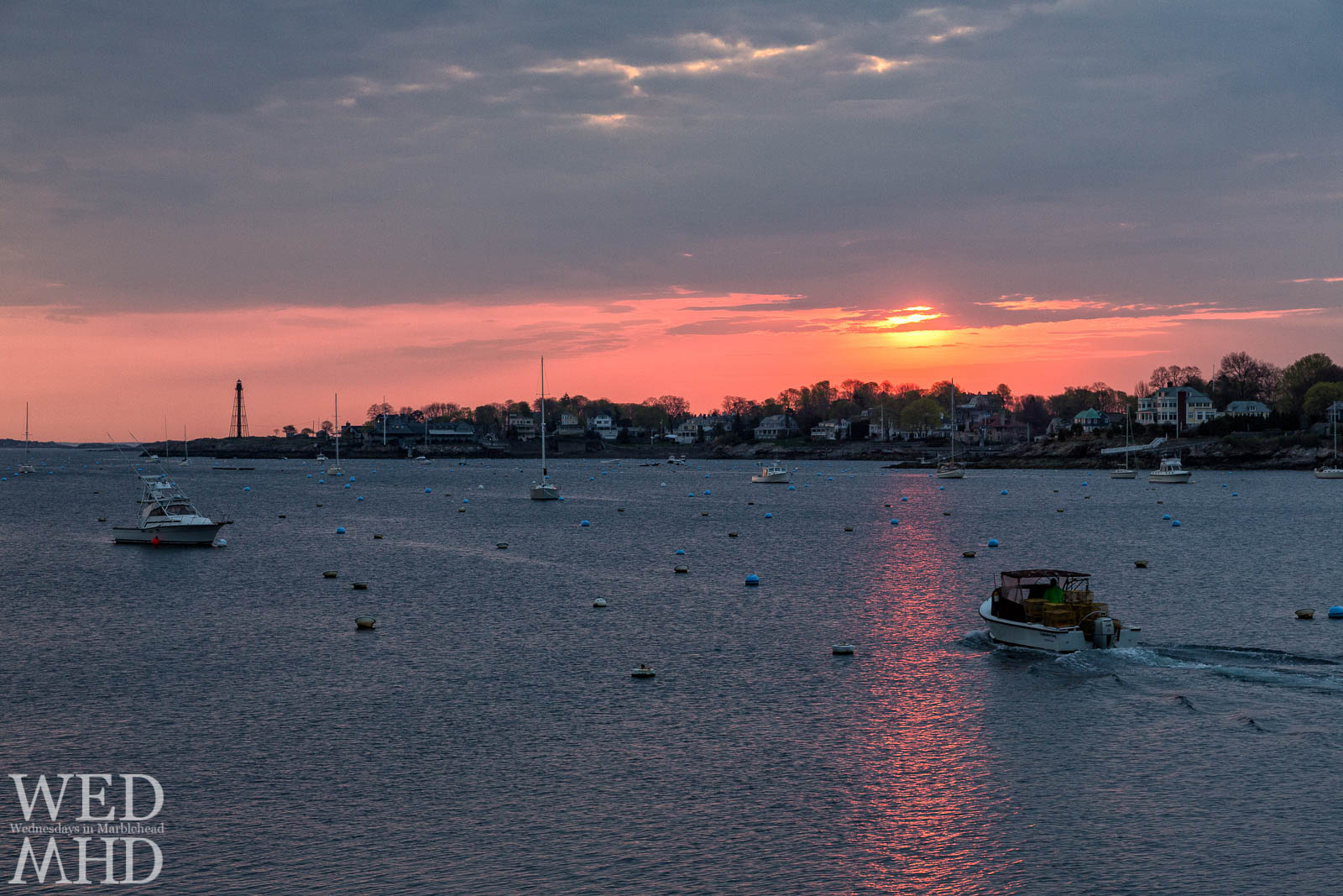 A lobsterman heads out of Marblehead Harbor as the sun rises in early May