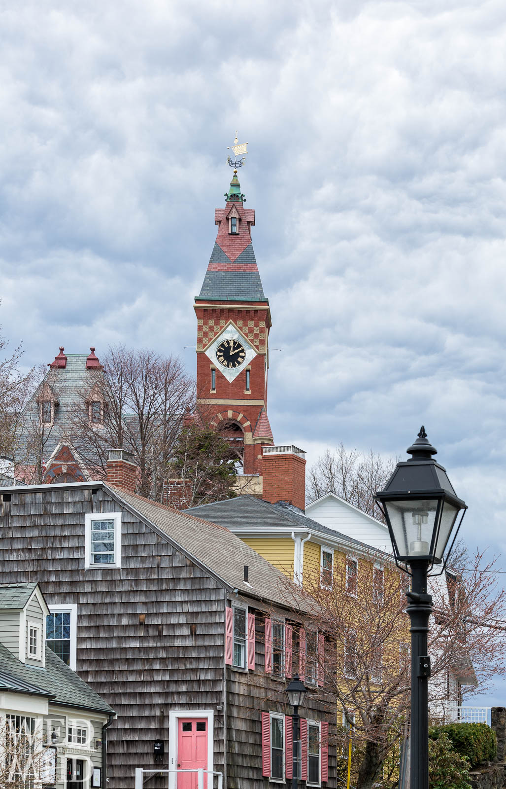Abbot Hall towers over houses along Washington Street including one with pink shutters