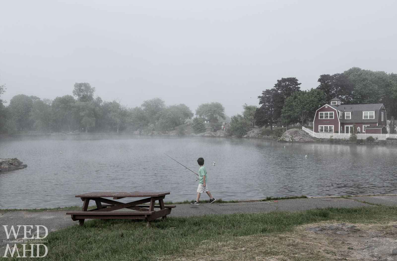 A boy walks around Redd's Pond looking for the fishing spot