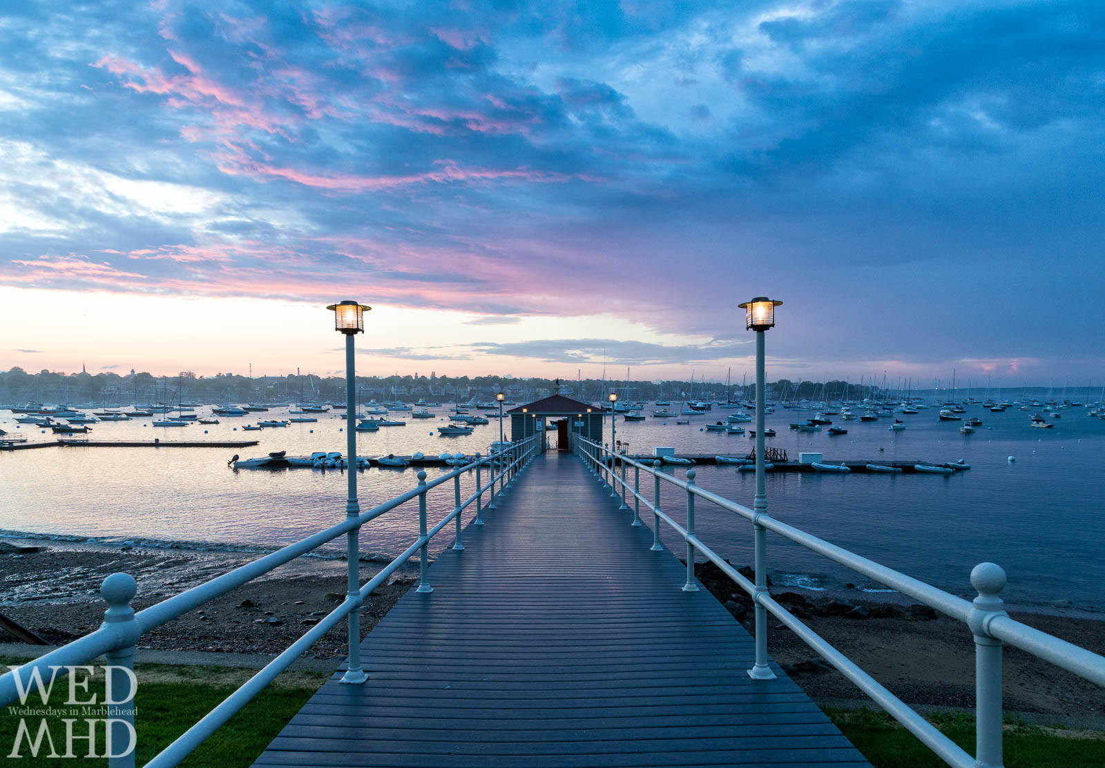 The beautiful pier of the Eastern Yacht Club is seen at sunset with purple clouds in the distance