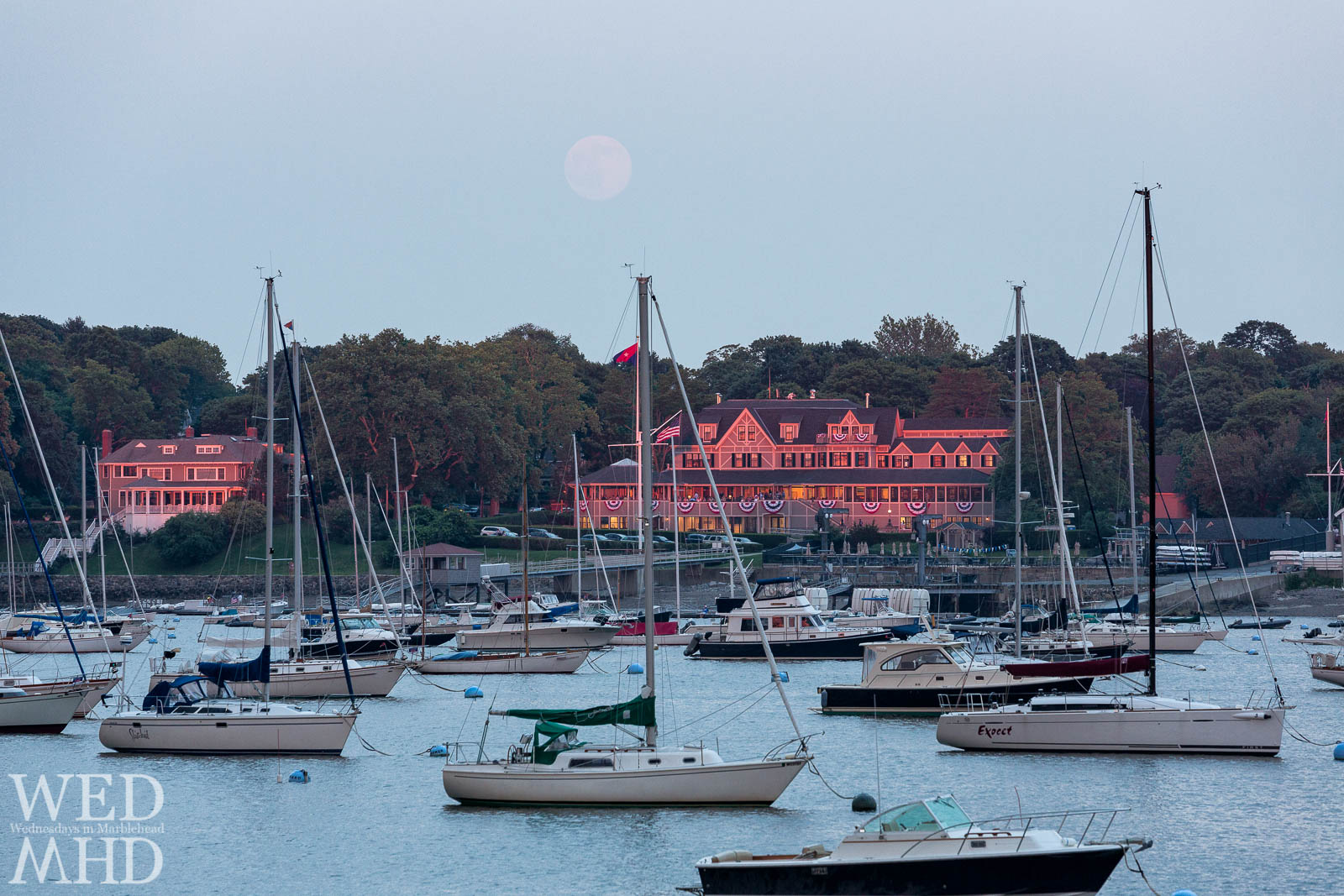 The Eastern Yacht Club glows red as the full moon rises overhead