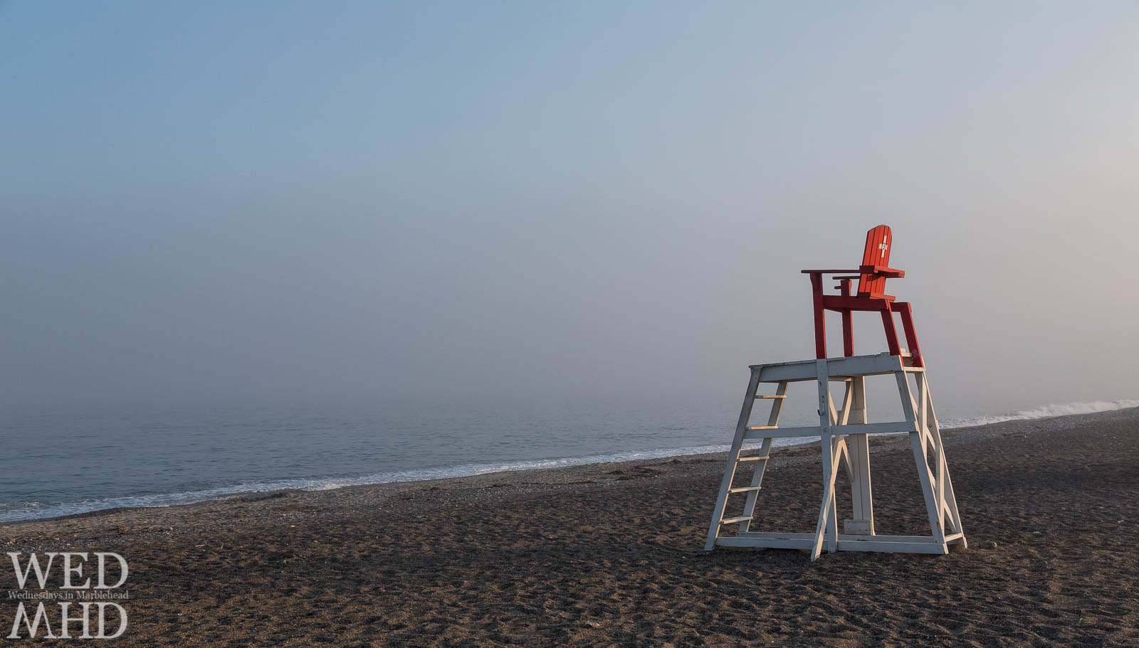 A lifeguard chair stands alone on an empty Devereux beach while fog obliterates the horizon