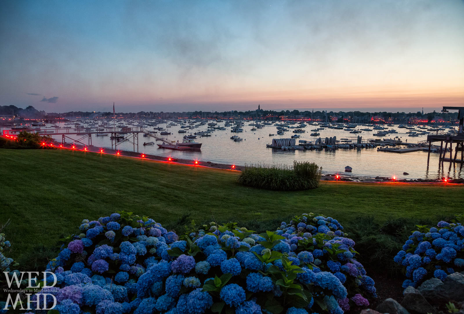 Flares are seen lighting up the harbor on the Fourth of July in Marblehead