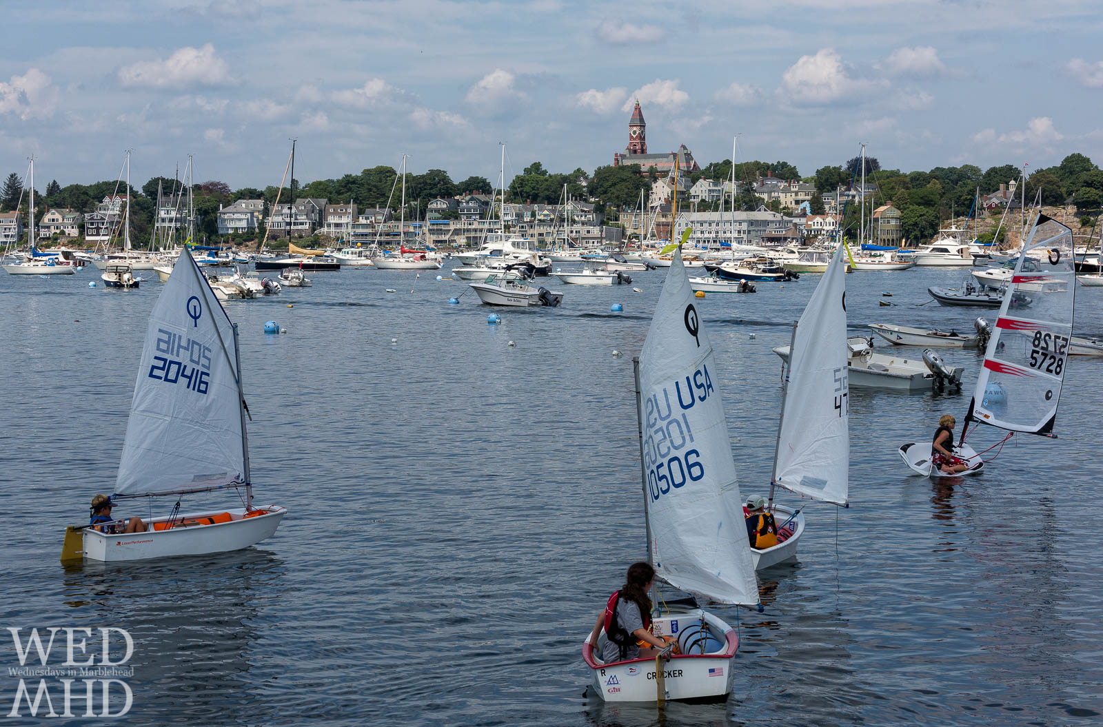 The start of Marblehead Junior Race Week features members of the Pleon heading out in Optis