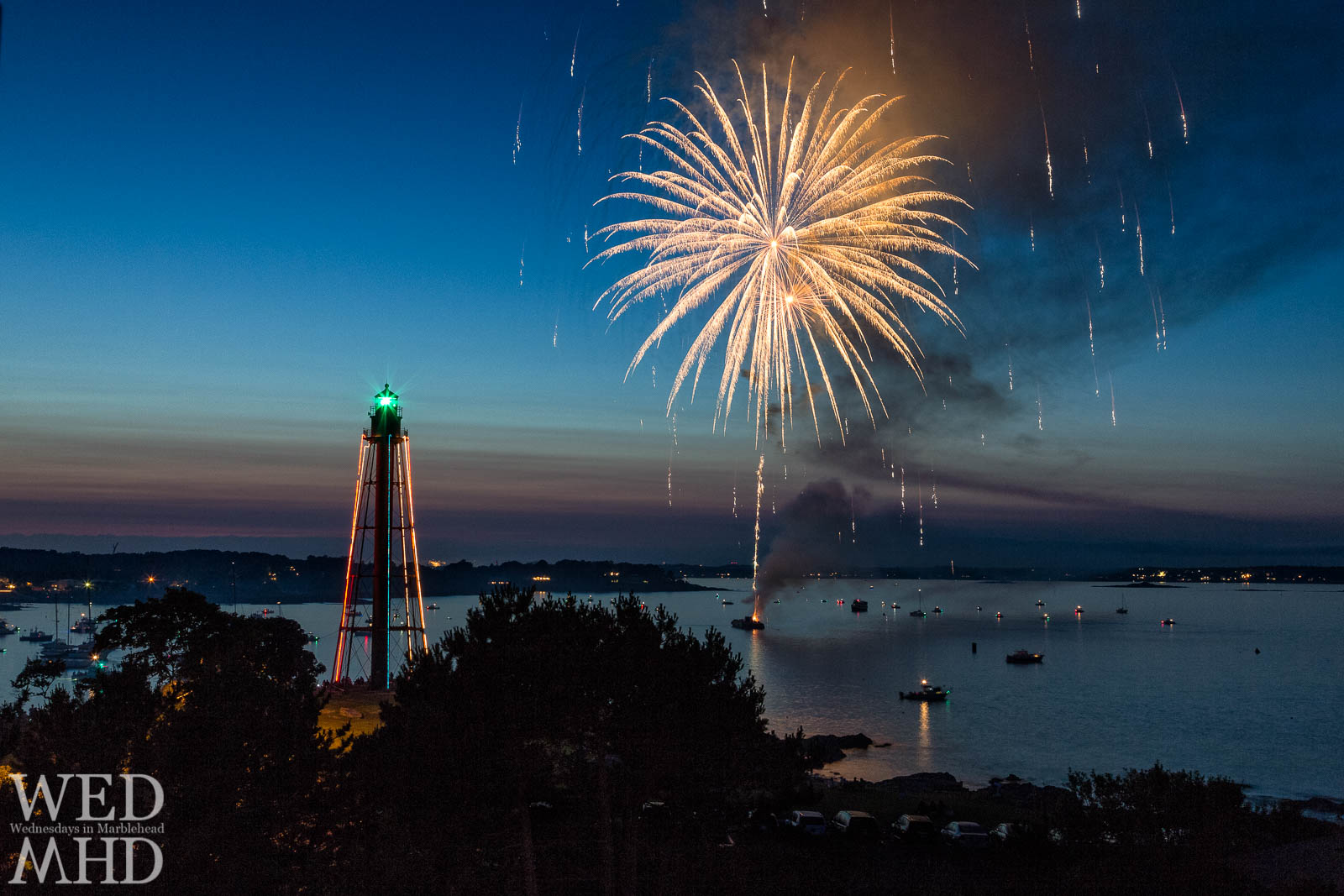 Fireworks explode over Marblehead Harbor with Marblehead Light standing tall on the Fourth of July
