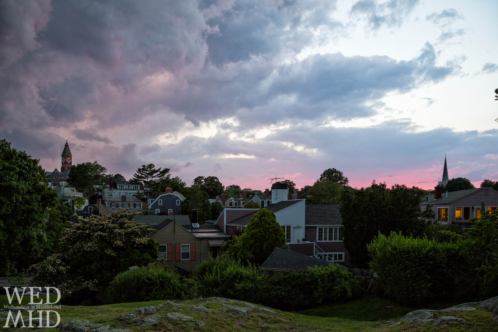 A coming storm casts pink hues at the horizon and purple light in the clouds
