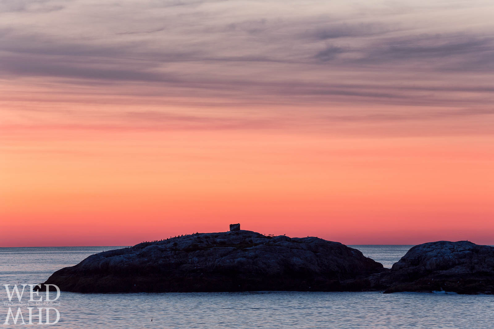 Marblehead Rock in silhouette against the red color of dawn