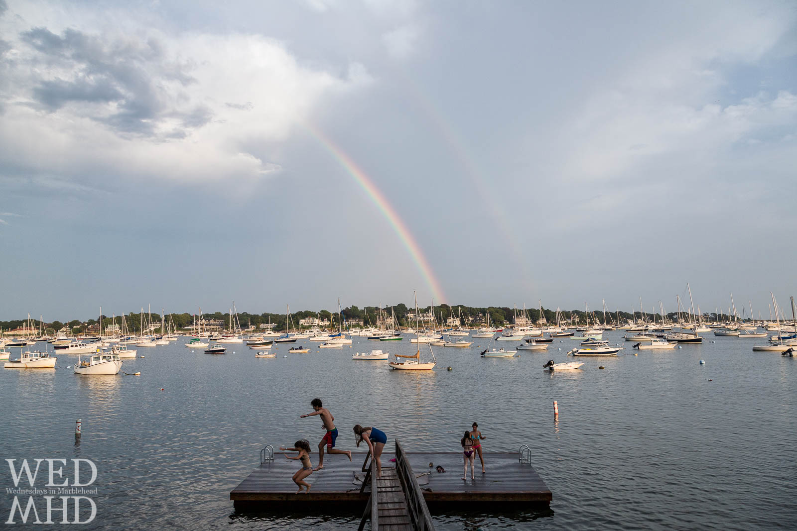 Kids jump off the bridge at Crocker Park with a rainbow visible over Marblehead Harbor