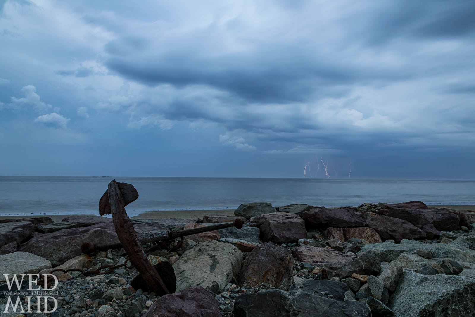 A cluster of lightning bolts seen off the shore at Preston Beach with the familiary anchor nestled among rocks