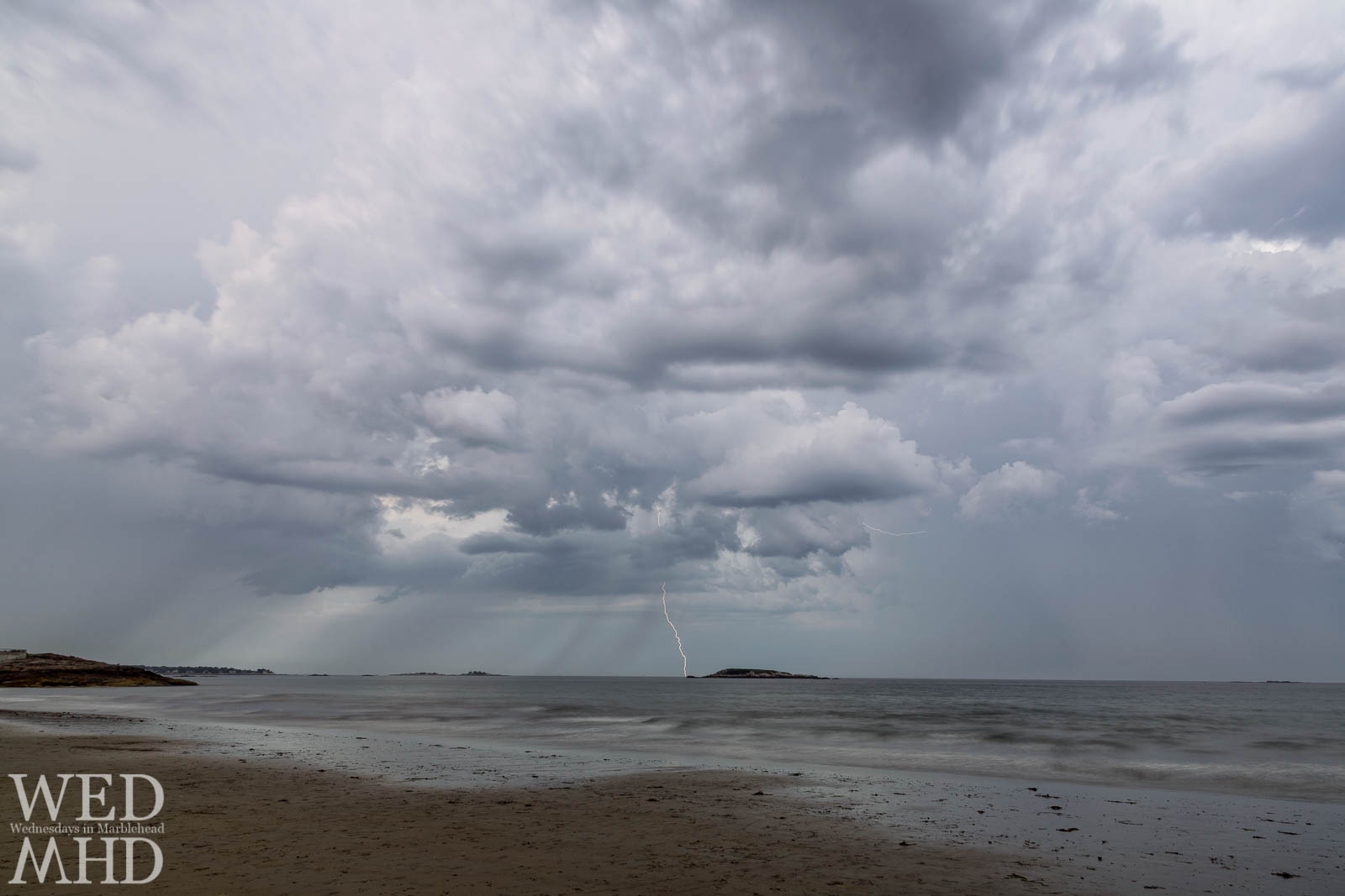 A bolt of lightning misses hitting Ram Island in the waters of Preston Beach