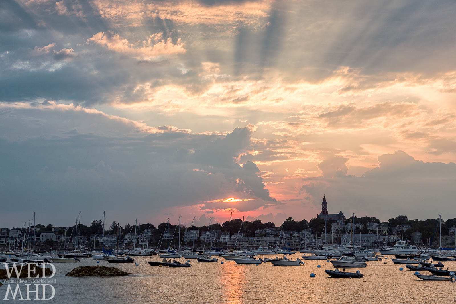An explosive sunset forms rays of light over Marblehead Harbor and Abbot Hall