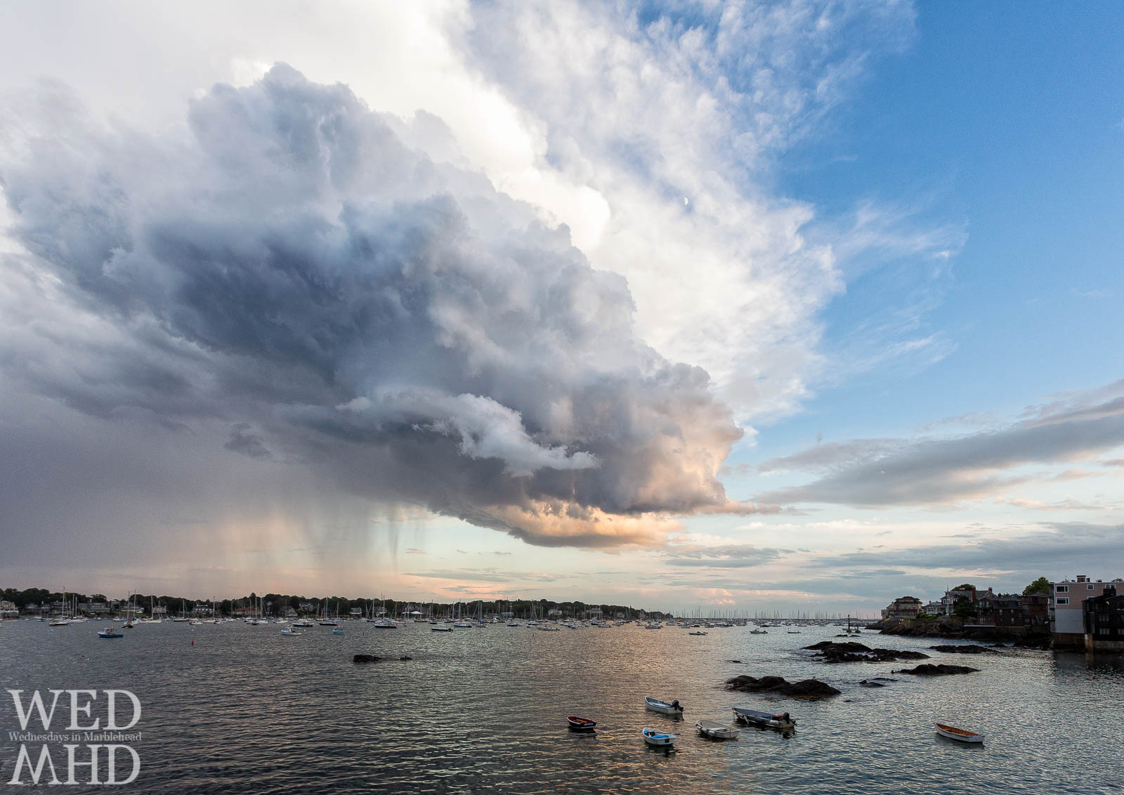 A storm cloud pours rain over Marblehead Neck as it is lit by sunset's glow
