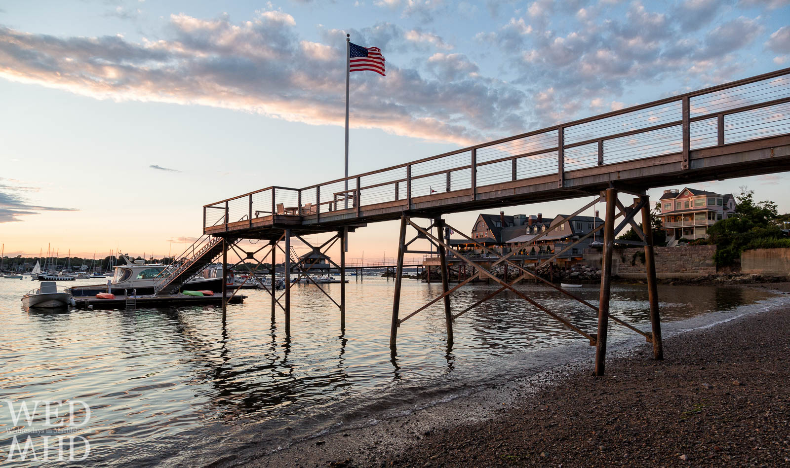 Old Glory flies high from a private pier along Marblehead Neck with the Corinthian Yacht Club seen in the distance