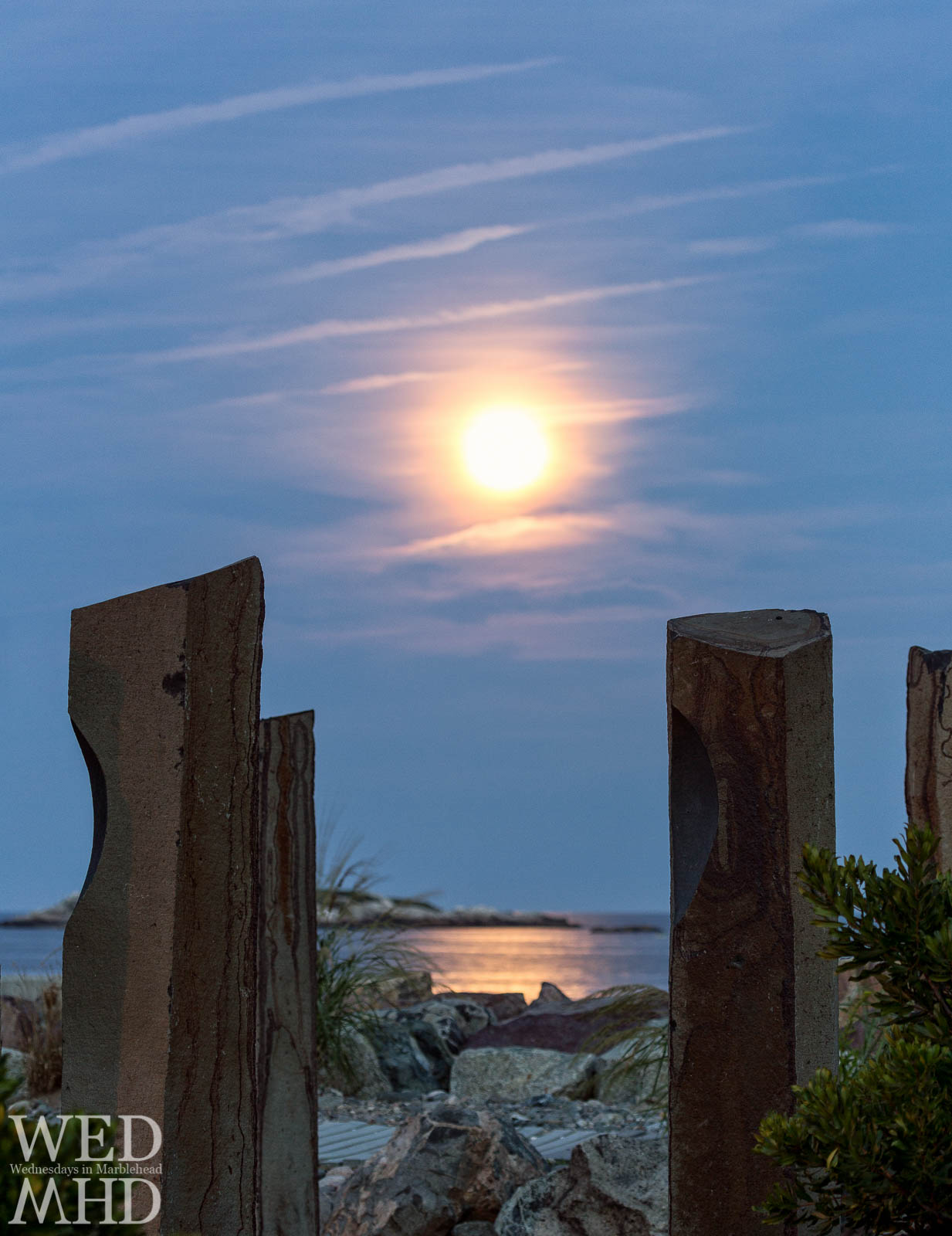 A full moon rises over the sun circle at Preston Beach and Beach Bluff Park