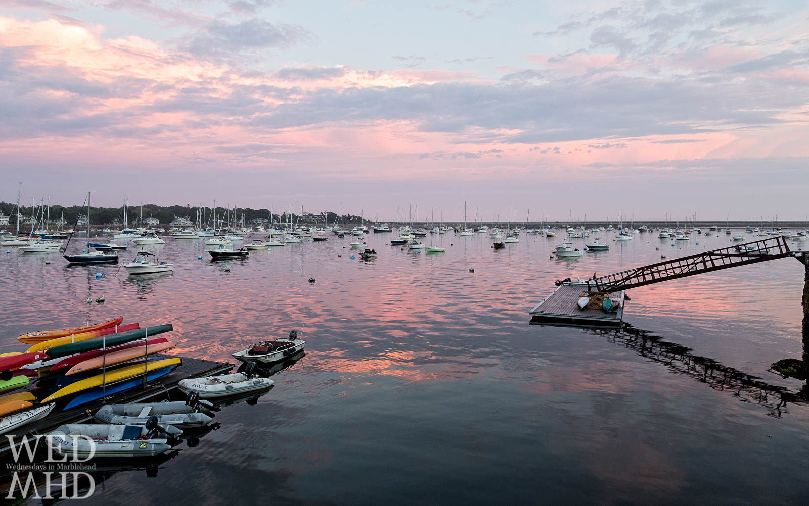 Kayaks add color to this pink sunset over Marblehead Harbor captured on a late Spring day