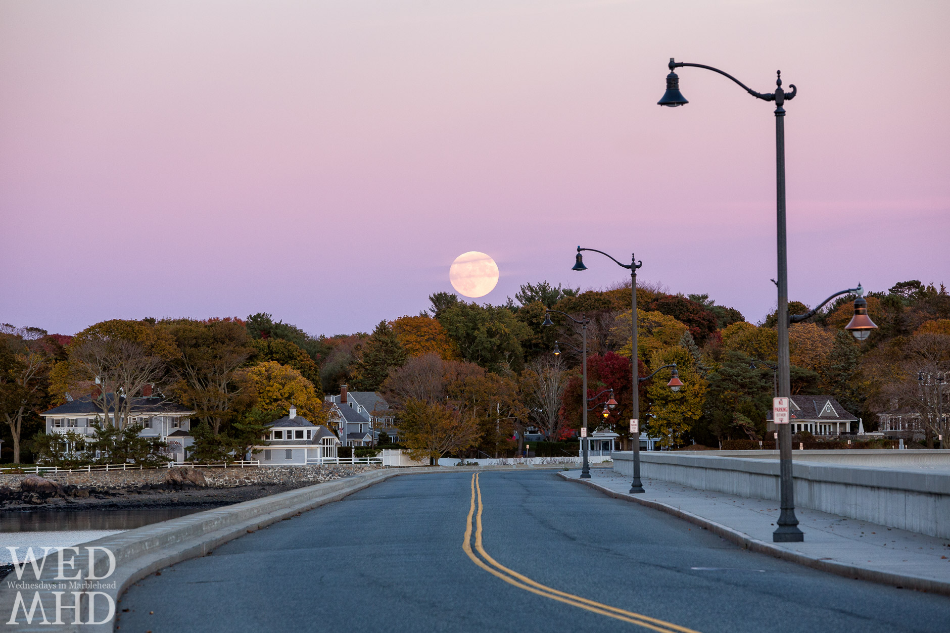 The full Hunter's moon rises over the causeway in Marblehead amidst peak foliage on the Neck