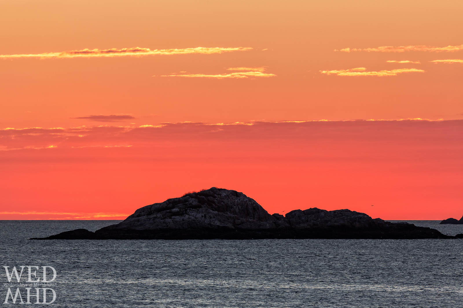 The red glow of dawn surrounds Cormorant Rock off Marblehead harbor