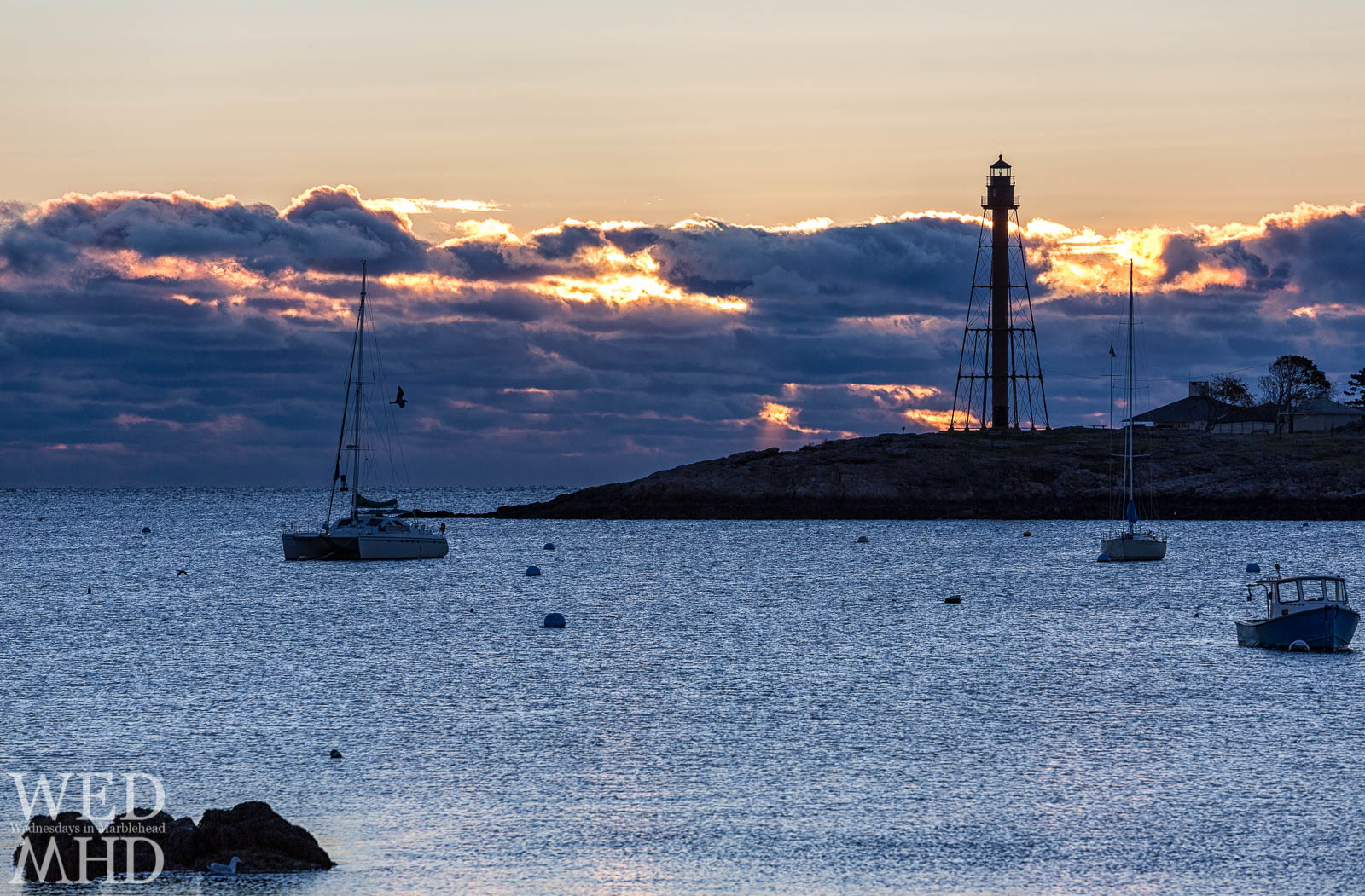 Rays of sunlight pour through a cloudbank on a cold morning in Marblehead