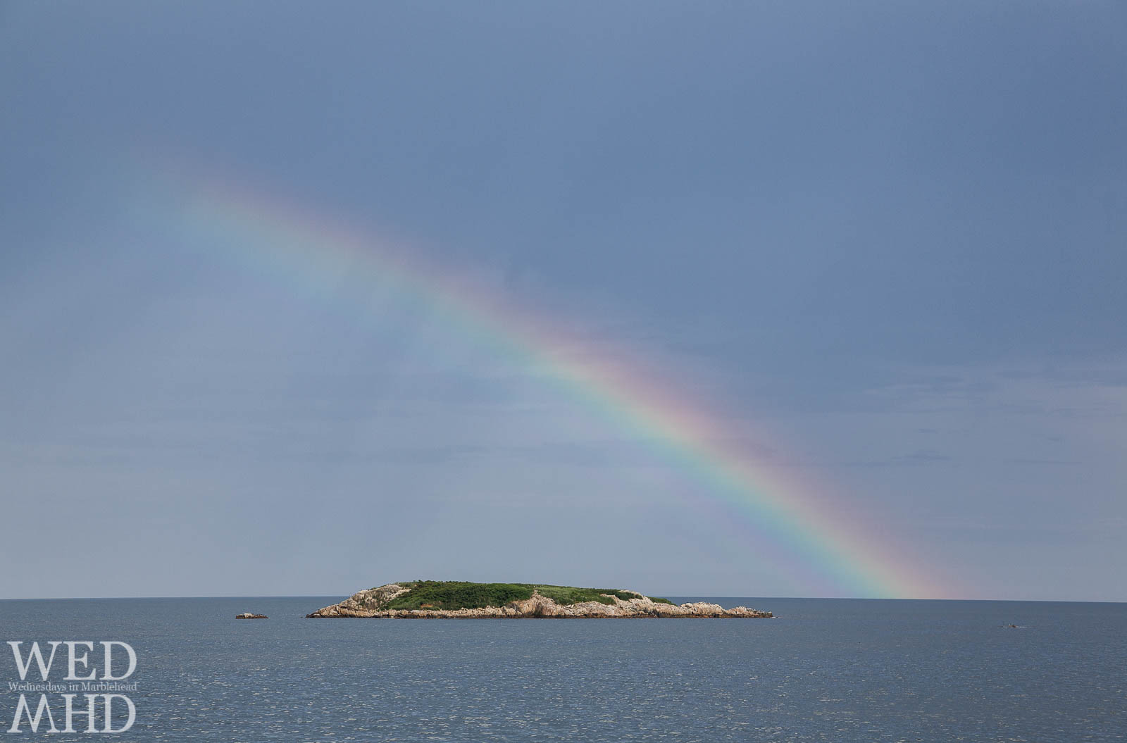 A midsummer rainbow forms over Ram's Island off Marblehead