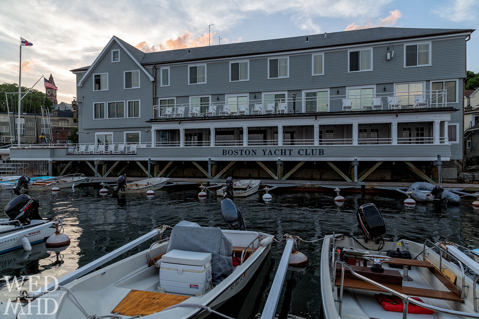A glimpse of Abbot Hall at sunset behind the full facade of the Boston Yacht Club captured at the end of a Summer day