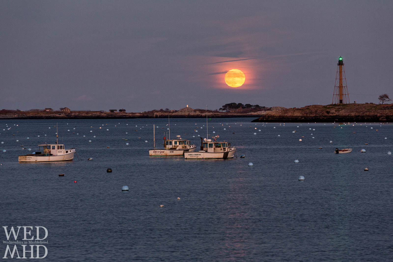 The full Beaver moon rises over Marblehead Harbor and a boat named Life is Good