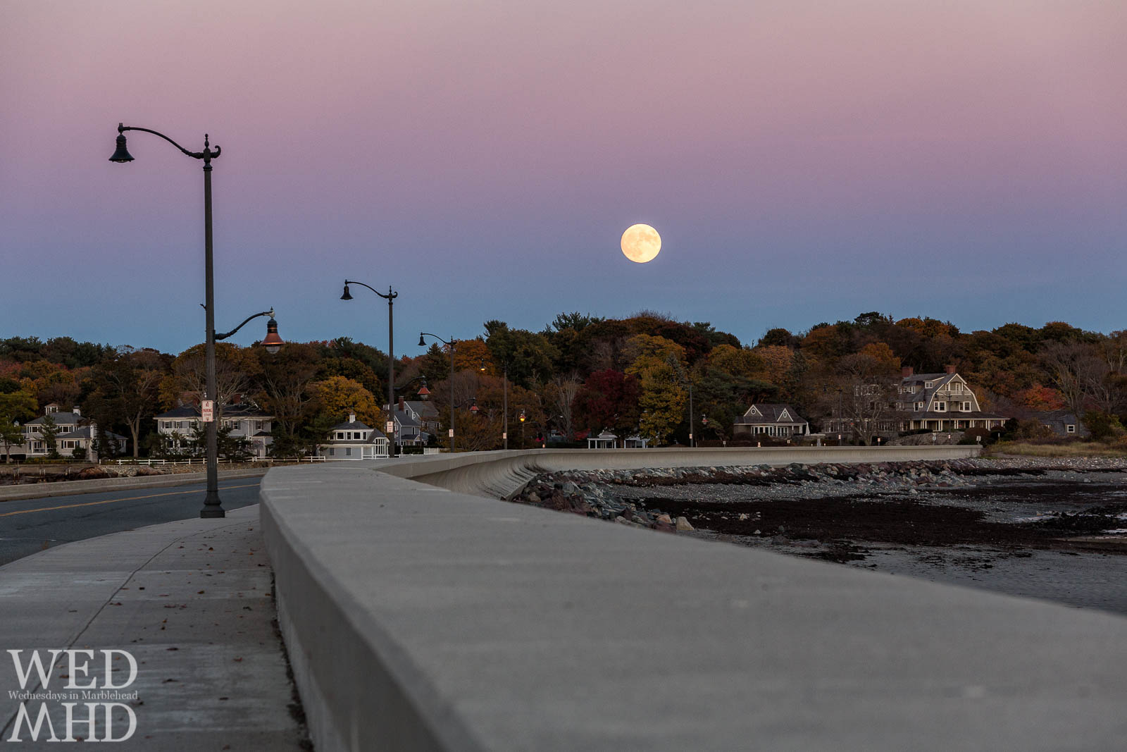 An image of the moonrise over the causeway with Fall colors visible along Marblehead Neck