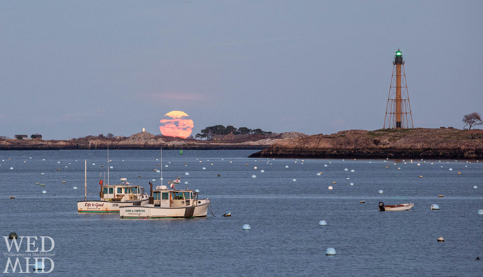 The Beaver moon is captured over Childrens Island with two working boats in Marblehead harbor on a perfect night for a moonrise