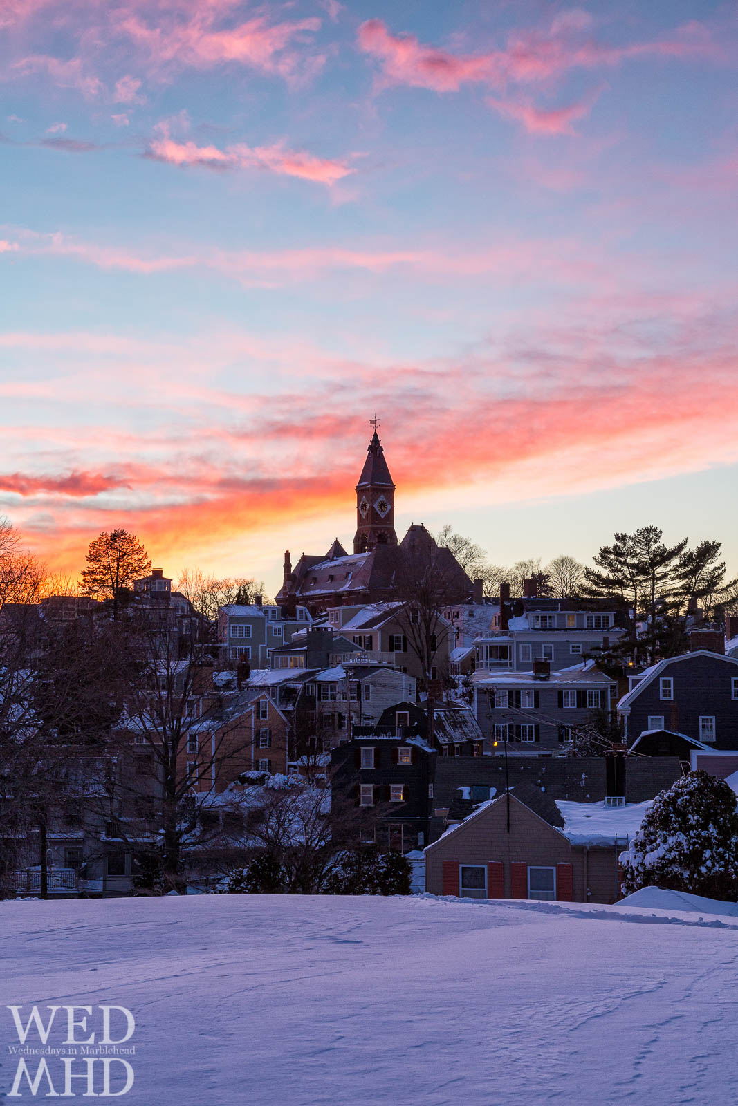 A beautiful sunset forms over Abbot Hall as seen from Crocker Park covered in a blanket of snow