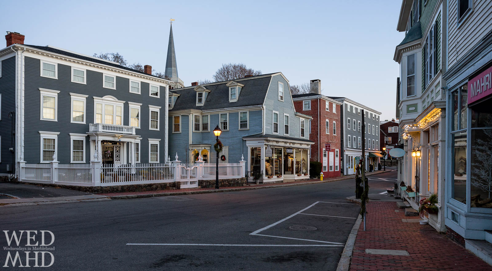 An early morning view of historic downtown Marblehead captures houses and shops with St. Michael's steeple rising above Washington Street