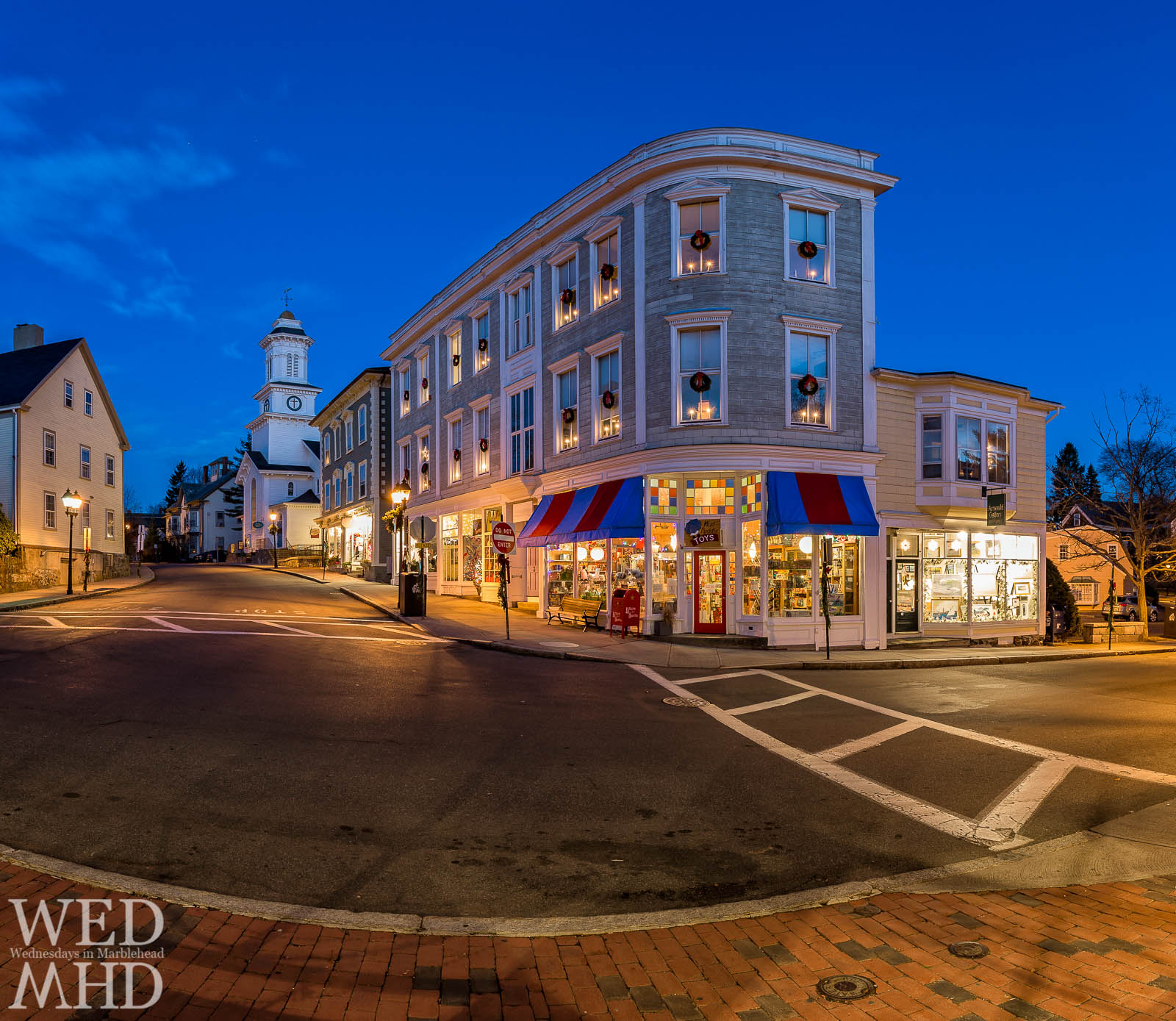 Holiday lights fill the windows or Arnould Gallery and Mud Puddle Toys on an early morning in historic downtown Marblehead