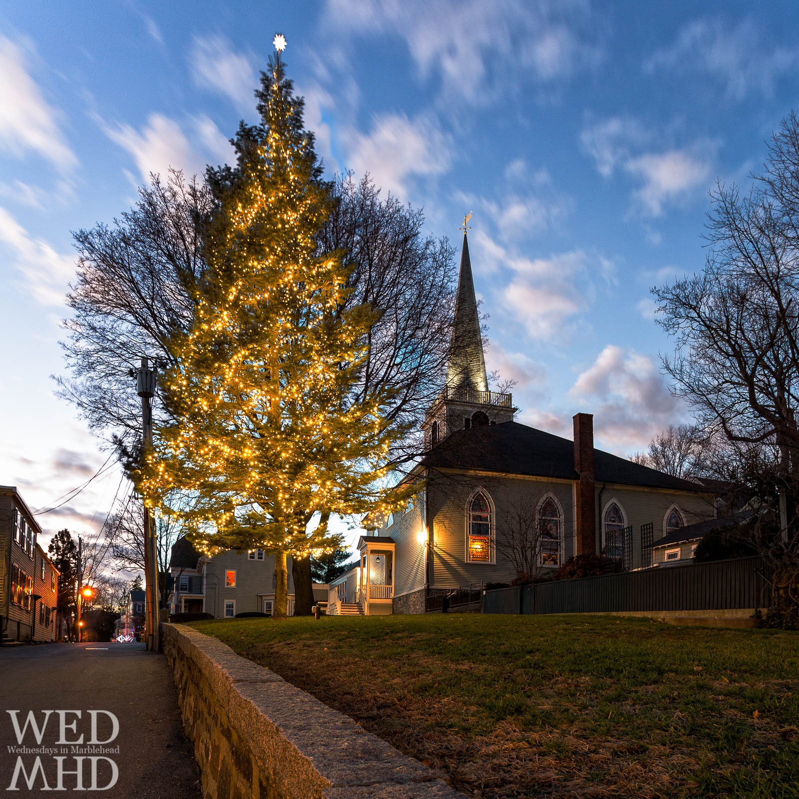 A Christmas tree is lit for the season on the grounds of St. Michaels Church with the new steeple now lit to match
