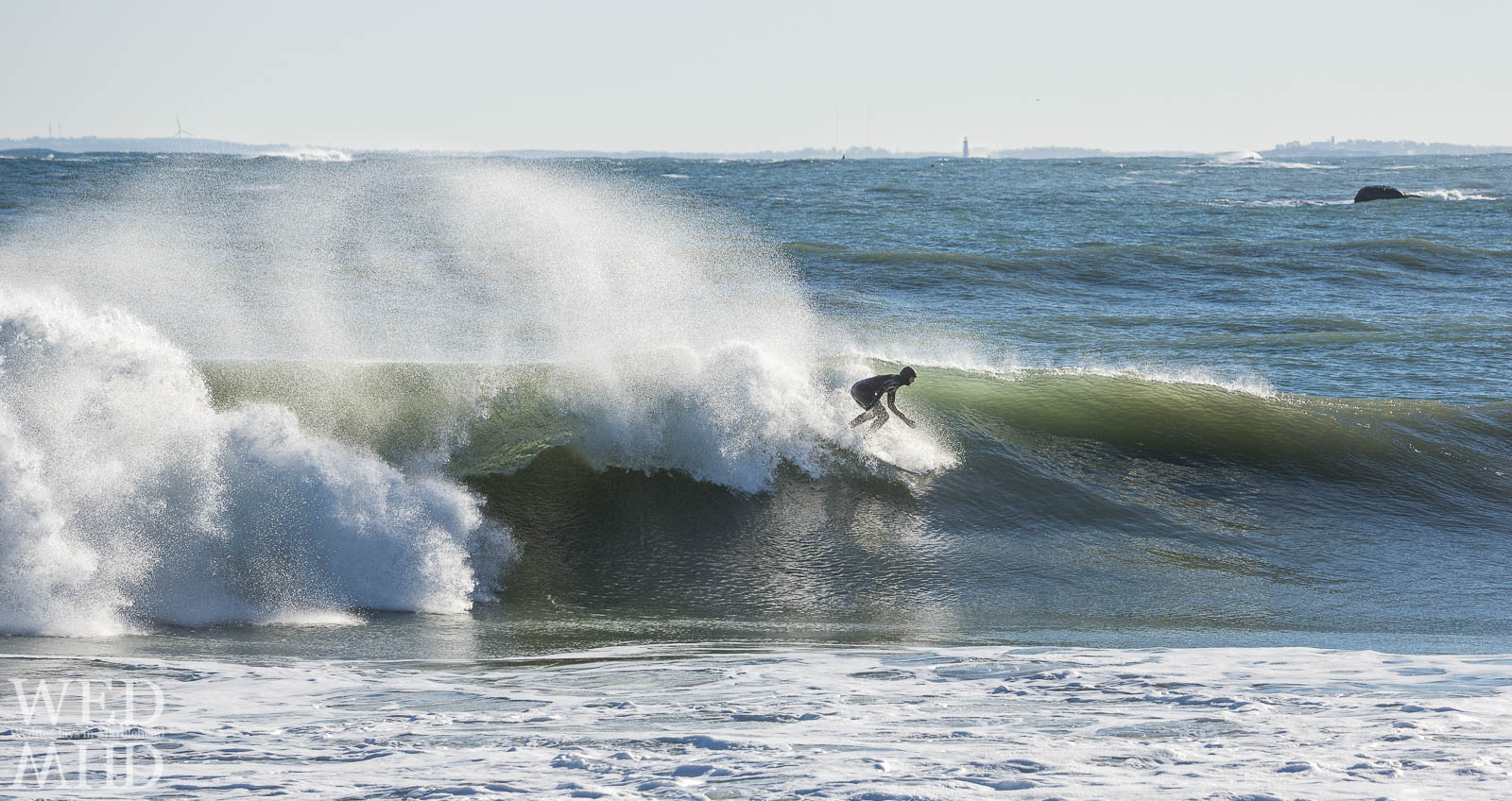 A surfer carves through a huge wave in Marblehead