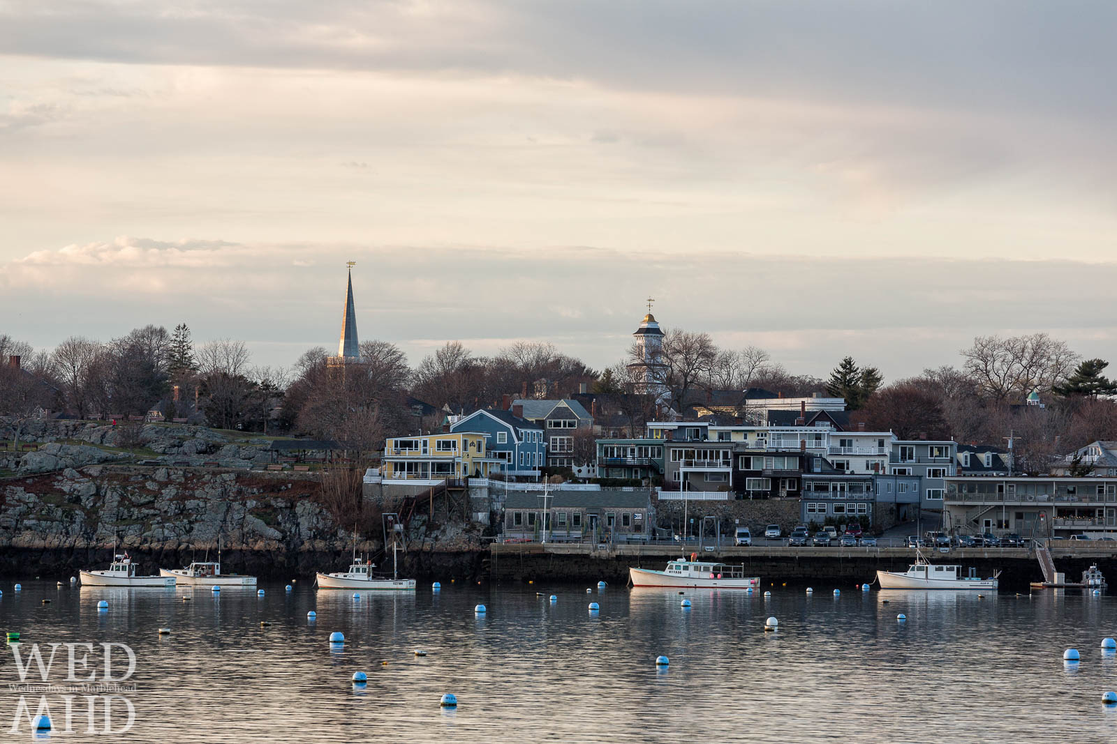 A few boats and waterfront homes with the tops of Grace Community Church and St. Michaels Steeple captured on Christmas Eve in Marblehead