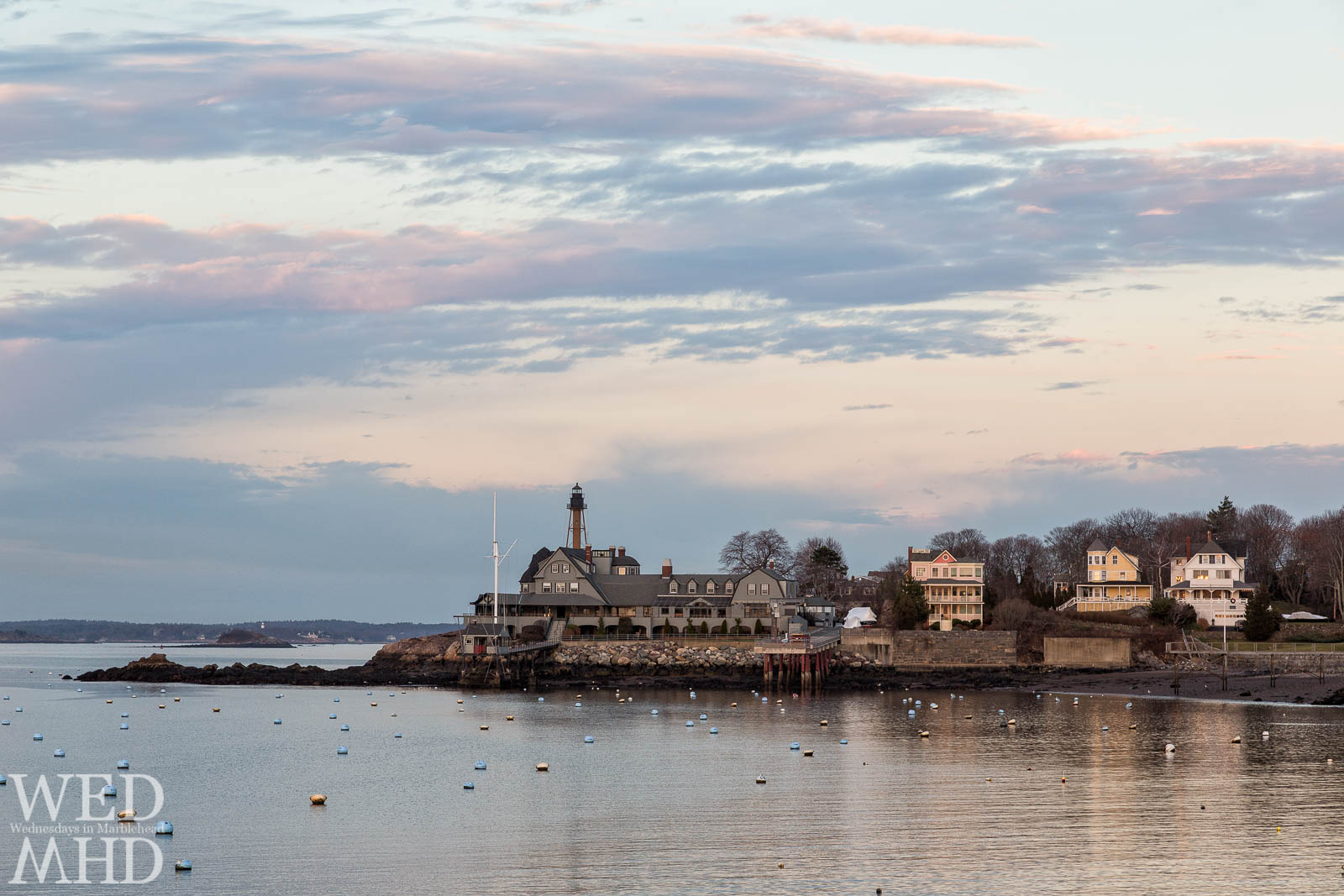 The last rays of sunlight reflect off Marblehead Light, the Corinthian Yacht Club and homes on the Neck captured on Christmas Eve in Marblehead
