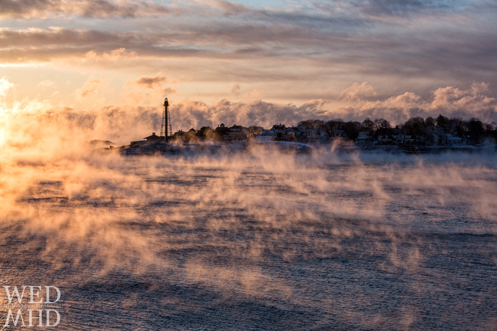 Tendrils of sea smoke dance across Marblehead Harbor at sunrise as arctic air causes water to form into steam
