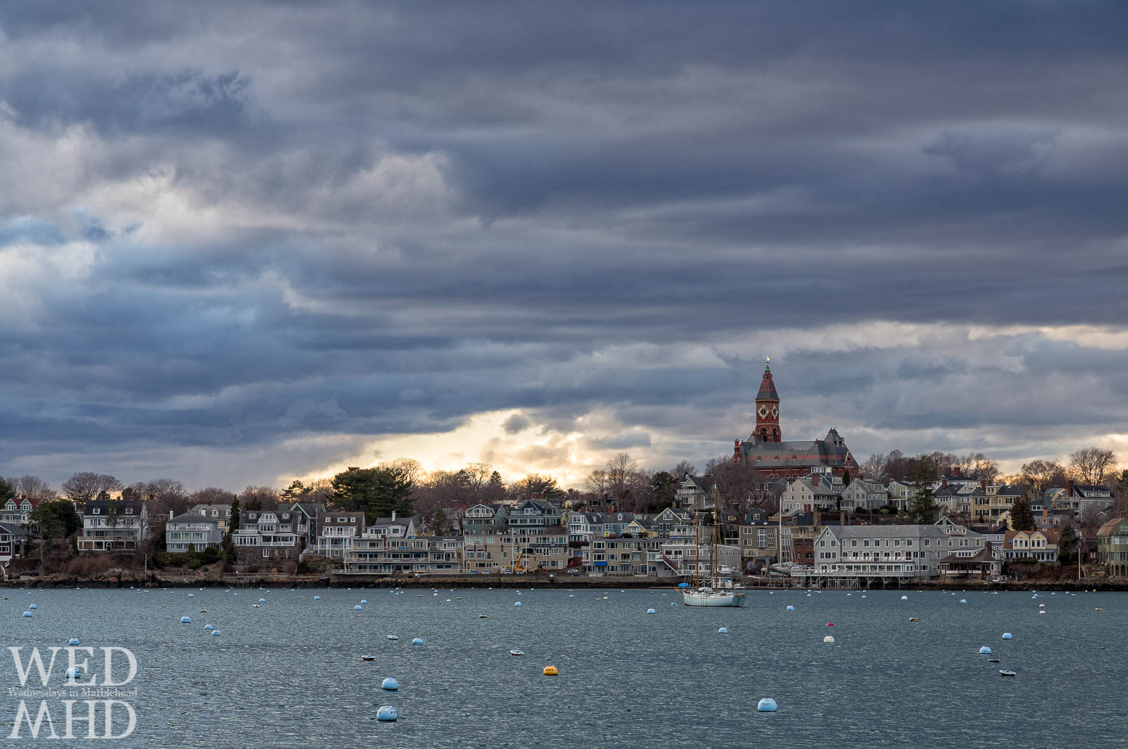 Houses along Marblehead Harbor appear in perfect clarity as a break in the clouds reveals golden light near sunset