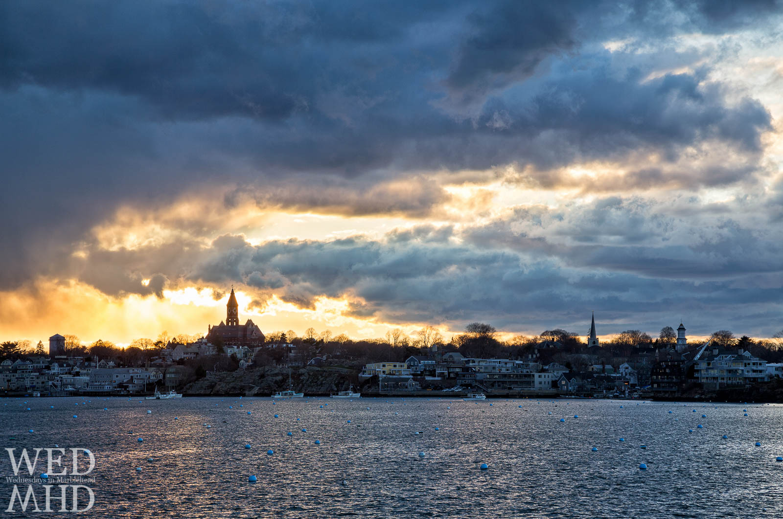 Golden light mixes with dramatic cloud structures over Marblehead's skyline featuring Abbot Hall, St. Michael's and Grace Community Church steeples.