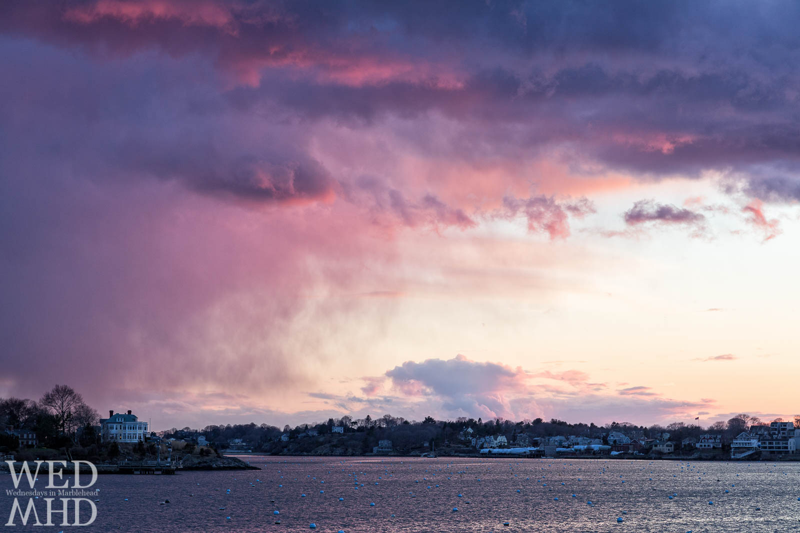 Pink clouds mix with a purple haze as a corker of a Marblehead sunset takes shape over a house on the neck
