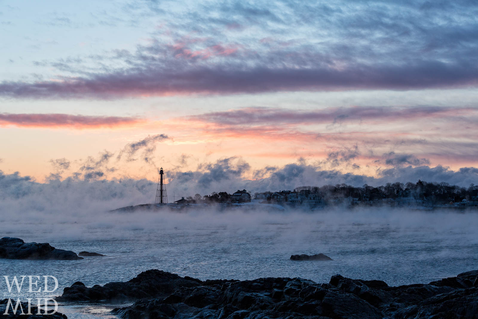 Sea smoke rises from Marblehead Harbor during an arctic cold front and is illuminated by the light of sunrise