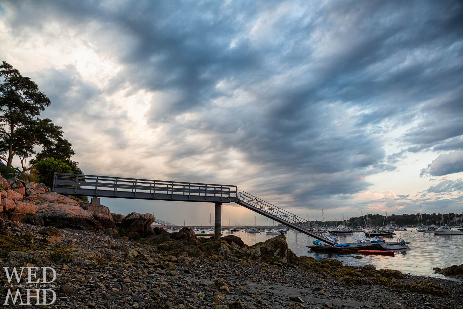 A dramatic sky encircles the pier at Parker Lane on a Summer evening in Marblehead